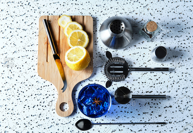 Top view of blue cocktail with ice cubes and sliced lemon on wooden board with barman tools on table