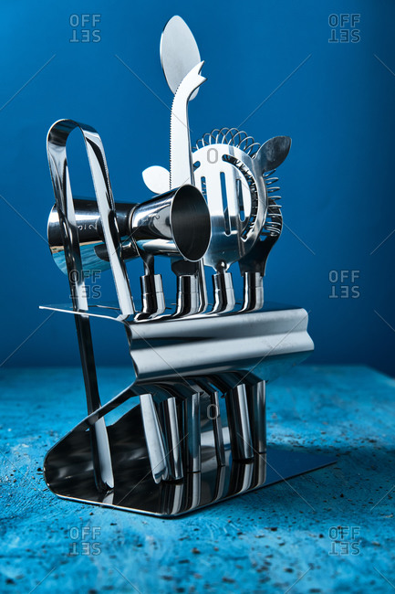 Professional contemporary shiny stainless steel barman equipment in stand on blue counter