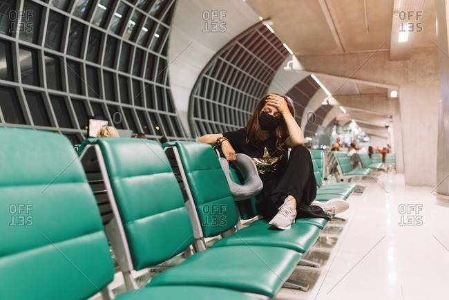 Frustrated female with mask touching head in airport