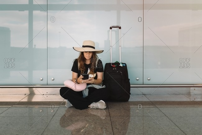 Young woman in hat and casual wear sitting in lotus pose on floor messaging on smartphone waiting for flight in airport
