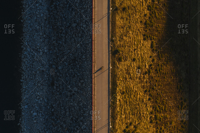 From above drone view of wonderful peaceful landscape of asphalt road on autumn day near a lake