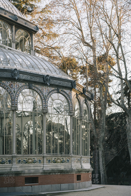 Geometrical ancient castle with glass windows reflecting trees, Palacio de Cristal, Retiro Park, Madrid, Spain