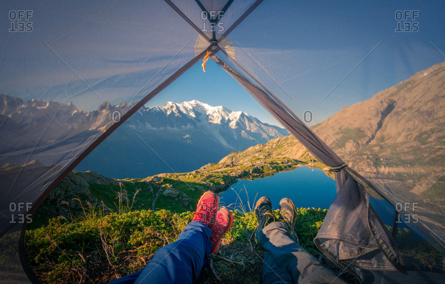 Crop pleasant hikers in colorful sneakers lying with crossed legs in small transparent tent near clear lake in mountains in sunny day in Chamonix, Mont-Blanc