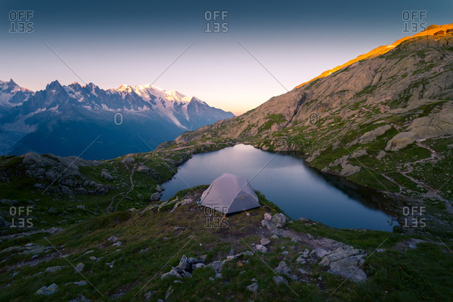 Crystal lake and tent in snowy mountains in sunlight