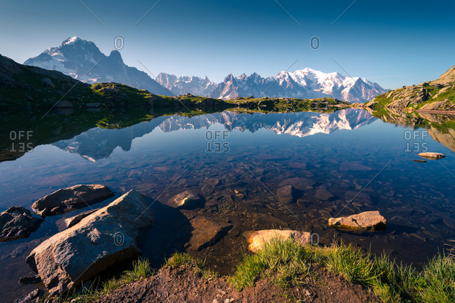 Crystal lake reflecting snowy mountains in bright day