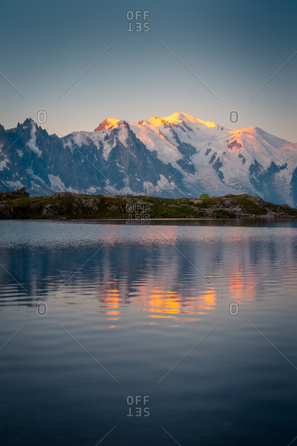 Amazing landscape of hilly shore and lake reflecting sunset in sky and snowy mountains in Chamonix, Mont-Blanc