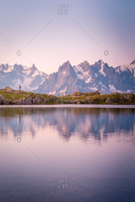 Lonely tourist on hilly shore reflecting in crystal lake in snowy mountains in sunlight