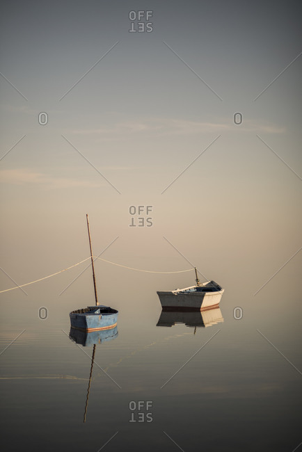 Still boats over pastel sky and empty calm ocean on the seaside