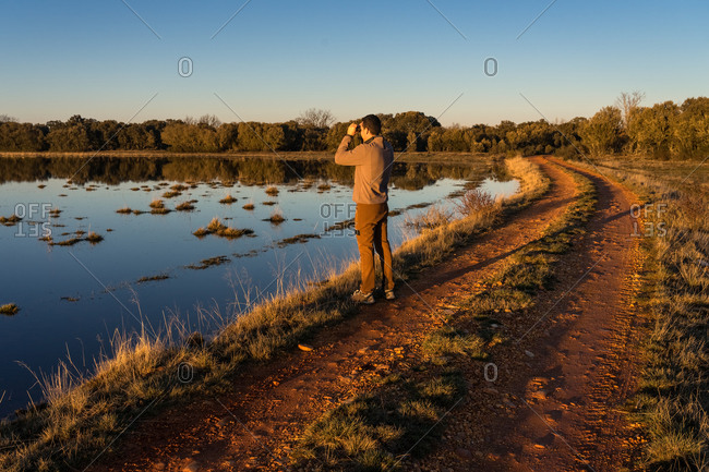 Side view of unrecognizable man looking through an old binoculars the fauna of a lagoon in Spain