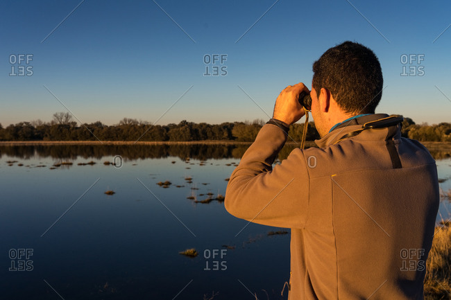 Back view of unrecognizable man looking through an old binoculars the fauna of a lagoon in Spain