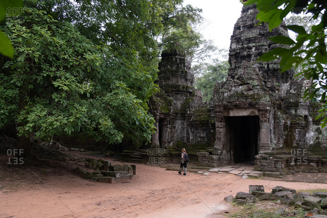 Back view of faceless traveler watching religious temple of Angkor Wat in Cambodia