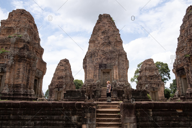 Side view of unrecognizable woman looking at ancient ruins of religious Hindu temple of Angkor Wat in Cambodia