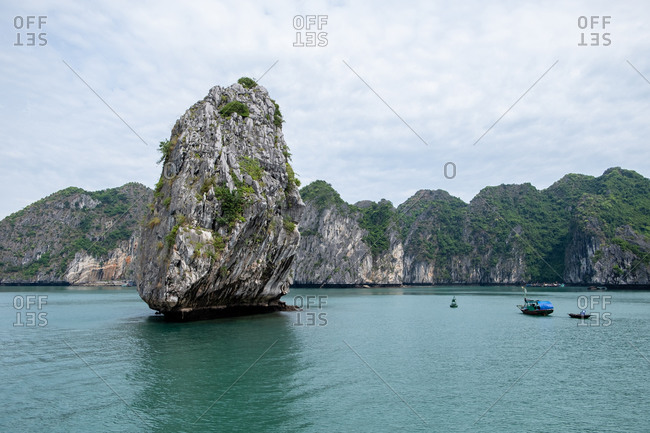 Magic scenery of solitude rock and boats in middle of Halong Bay in Vietnam