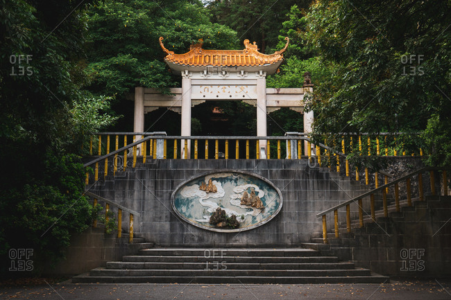 June 26, 2018: June 26, 2018: Exterior view of stone ornamental facade of oriental temple among lush vegetation in Qingxiu Mountain, Nanning, China