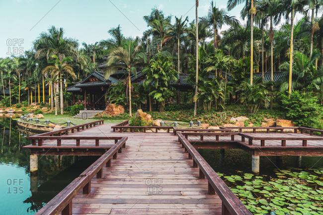 June 26, 2018: June 26, 2018: Walkway above tranquil lake in tropical park