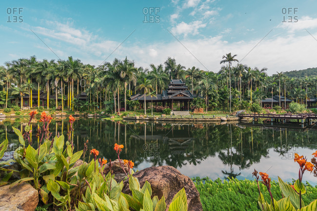 June 26, 2018: June 26, 2018: Landscape of tropical plants and palms on pond with oriental building in park of Qingxiu Mountain, Nanning