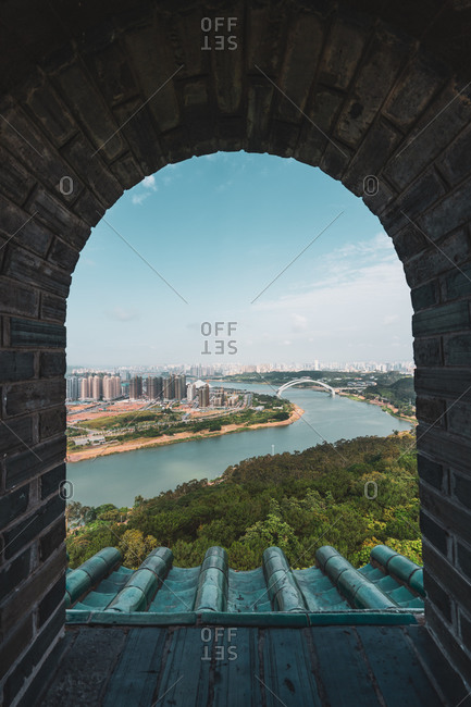 Shot through brick old window with view of cityscape of Nanning on river shore, China