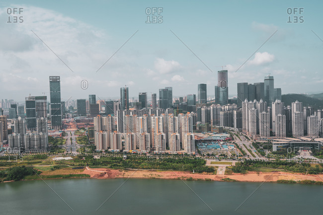 June 26, 2018: June 26, 2018: Aerial view of modern highrise city Nanning placed on shoreline of river with green vegetation, Guangxi, China