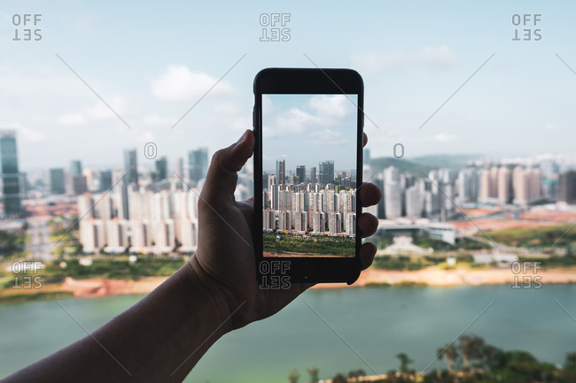 June 26, 2018: June 26, 2018: Crop hand holding smartphone and taking picture of contemporary city of Nanning from height, China