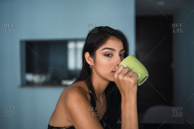 Beautiful passionate brunette Hispanic woman in dress looking at camera and holding mug of hot drink at table with volume in room