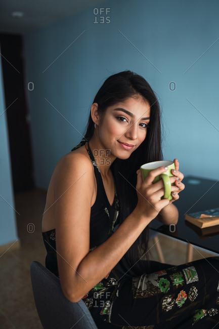 Side view smiling beautiful passionate brunette Hispanic woman in dress looking at camera and holding mug of hot drink at table with volume in room