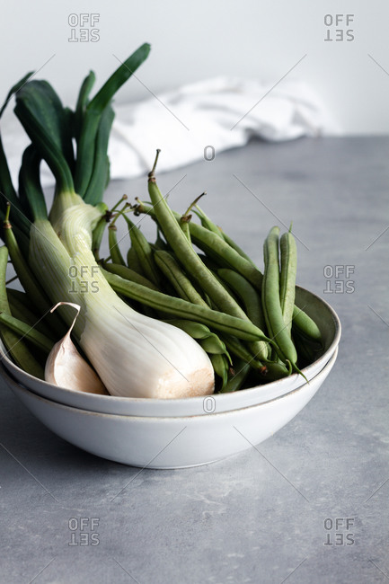 White bowl with garlic and green onion and green beans on table in kitchen