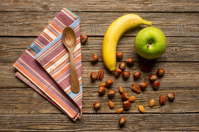Top view of apple and banana with nuts near spoon and towel on wooden table with healthy food
