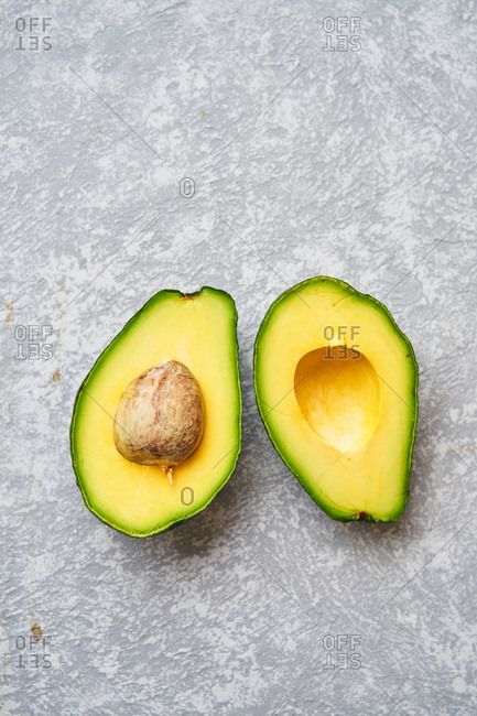 Top view of fresh ripe avocado cut in half on light grey texture background