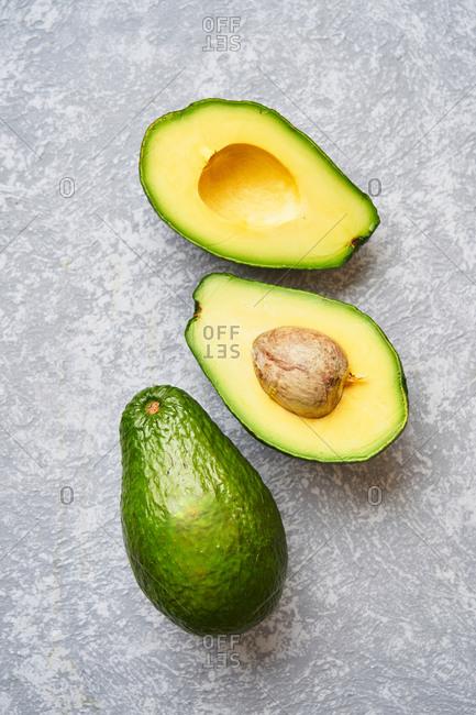 Cut avocado on grey texture background