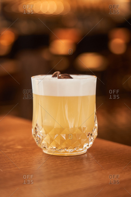 Glass of classic alcohol cocktail Whiskey Sour with lemon juice and egg white placed on wooden counter