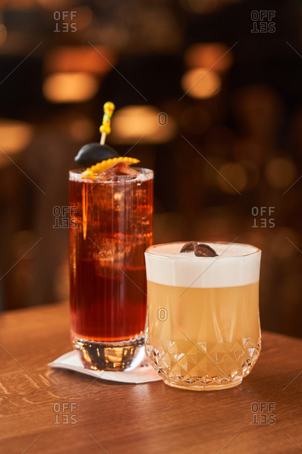 Cocktail with ice cubes decorated with stick with black olive and Whiskey Sour with lemon juice cocktail on wooden counter
