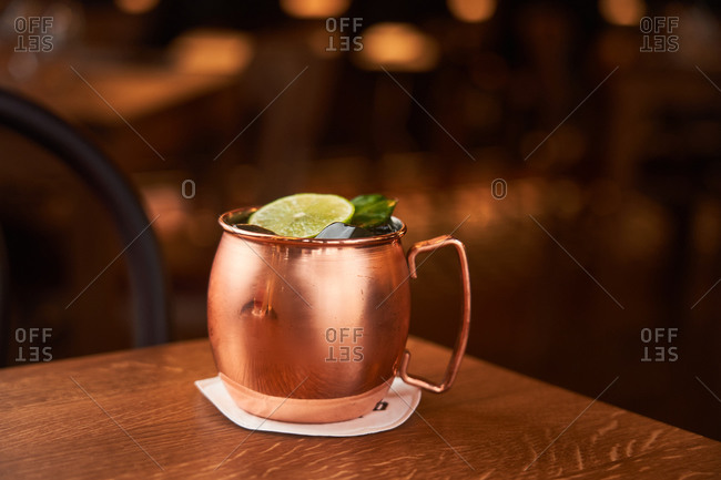 Classic alcohol cocktail Moscow Mule based on vodka with ginger beer and lime juice served in copper mug decorated with lemon slice on wooden table