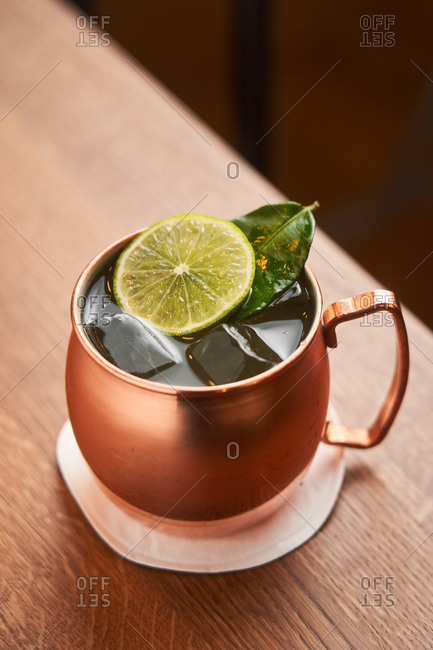 From above classic alcohol cocktail Moscow Mule based on vodka with ginger beer and lime juice served in copper mug decorated with lemon slice on wooden table