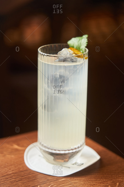 Vodka and tonic alcohol cocktail in highball glass decorated with ice and mint leaves on dark background