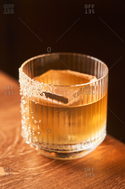 Short glass of amber alcohol whiskey cocktail with ice decorated with sugar placed on wooden counter with black background
