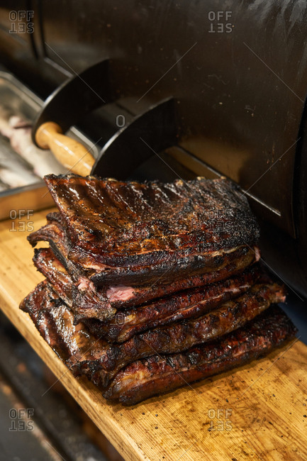 Composed stack of grilled juicy ribs on cutting board near barbecue