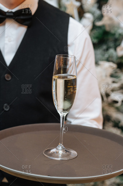 Unrecognizable male waiter holding tray with glass of white wine during party in restaurant