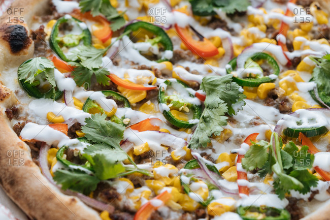 from above closeup of  tasty baked pizza with minced meat and corn decorated with bell pepper and parsley with mozzarella cheese in cafe