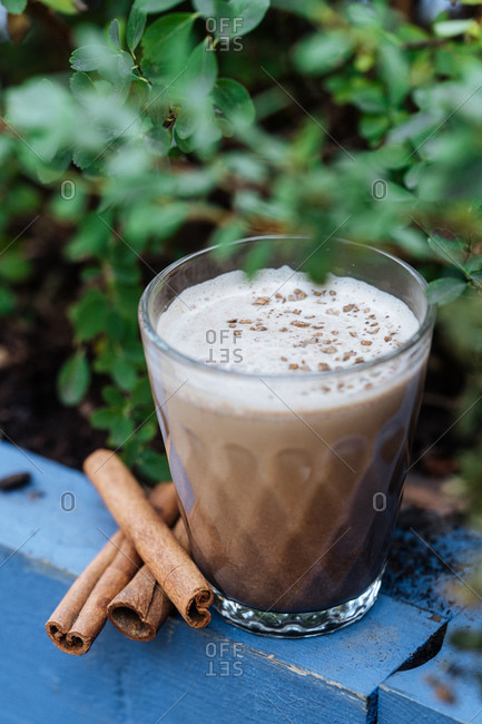 From above refreshment beverage eggnog with cinnamon in glass cup on rustic surface