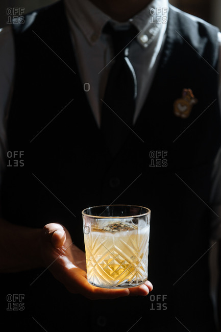 Crop barista in apron holding glass of fresh juicy drink shining in sunlight