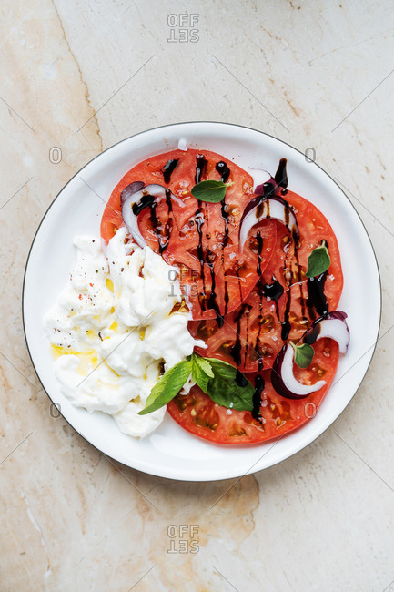 From above ripe red sliced tomatoes with red onion sour cream and herbs in plate on table
