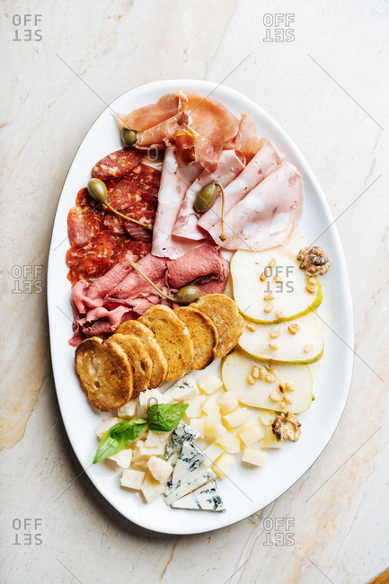 Top view of white oval plate with slices of several types of sausage served with olives fried rounded pieces of bread cheese decorated with fresh mint and slices of pear in restaurant