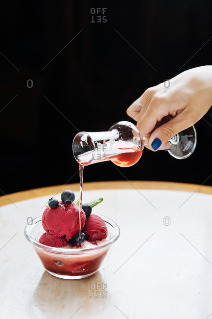 Cropped unrecognizable woman hand pouring a red beverage from a glass on purple scoops of ice cream in glass bowl decorated with fresh blueberry and mint and served in restaurant