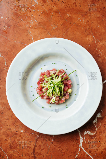 Top view of ceramic white plate with slices of red tuna and cheese decorated with pieces of cucumber and spices in restaurant