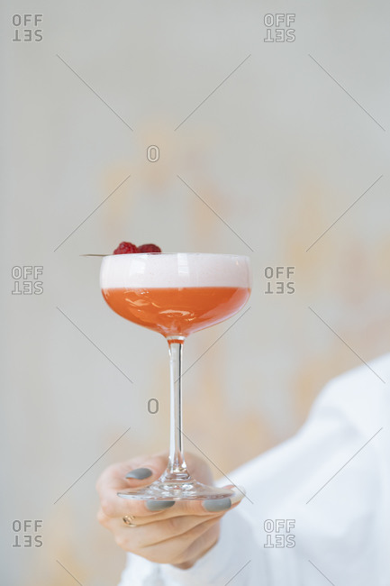 Anonymous waiter in white shirt holding delicious red cocktail in stylish glass decorated with fresh raspberry
