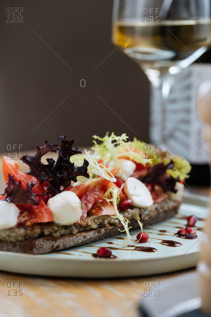 Delicious rye bread smeared with sauce and served with slices of tomatoes colorful lettuce and cheese on table with glass of wine in restaurant