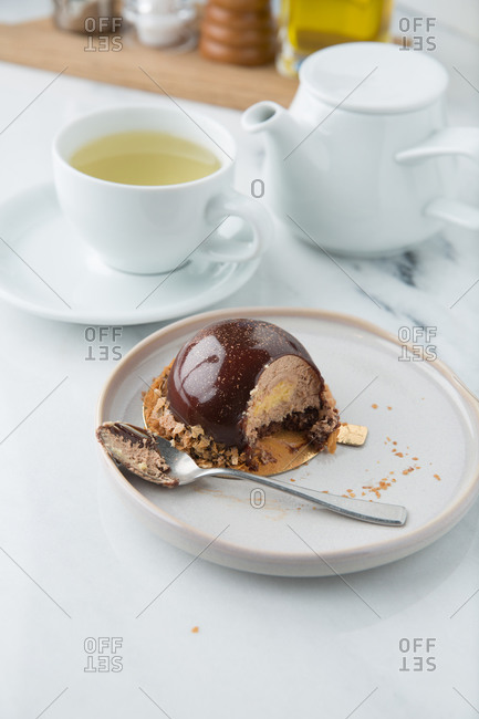 Haute cuisine confectionery product of creamy mousse in chocolate decorated with cereals on plate with spoon