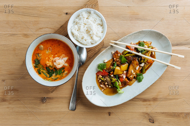 Top view of colorful vegetables in oval plate with chopsticks on wooden table with spicy seafood soup and with of boiled rice