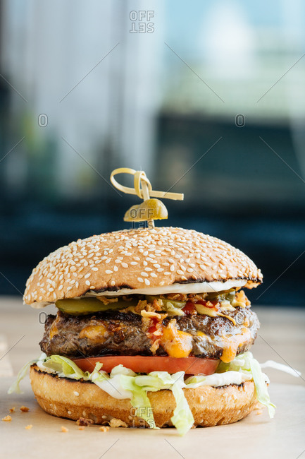 Closeup of juicy burger with tasty cutlet slices of tomatoes lettuce and cucumbers between soft roasted buns in restaurant