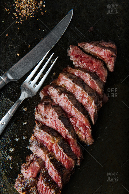 Top view of medium rare slices steak on table with fork and knife in restaurant